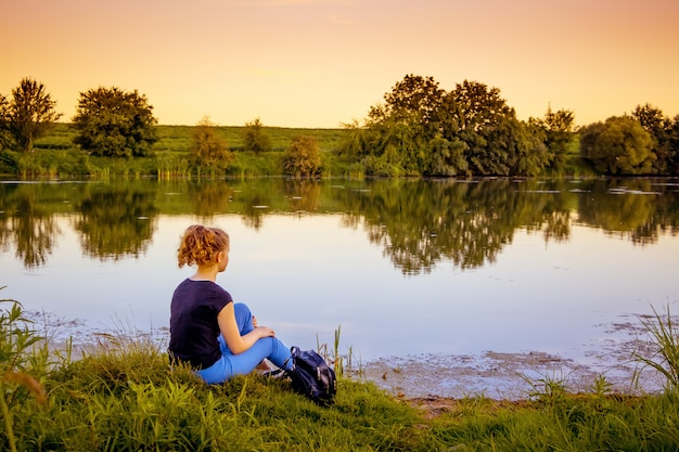 Молодая девушка сидит на берегу реки и любуется природой во время заката. здоровый образ жизни, пребывание на природе