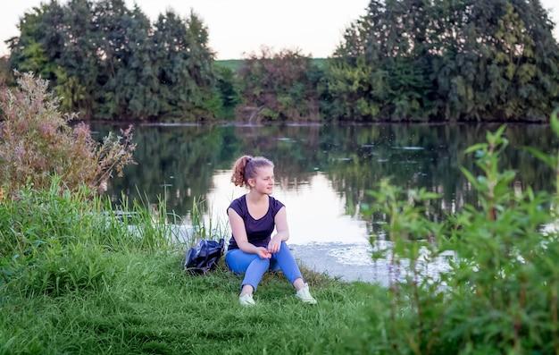 Молодая девушка сидит на берегу реки и любуется природой. здоровый образ жизни, пребывание на природе