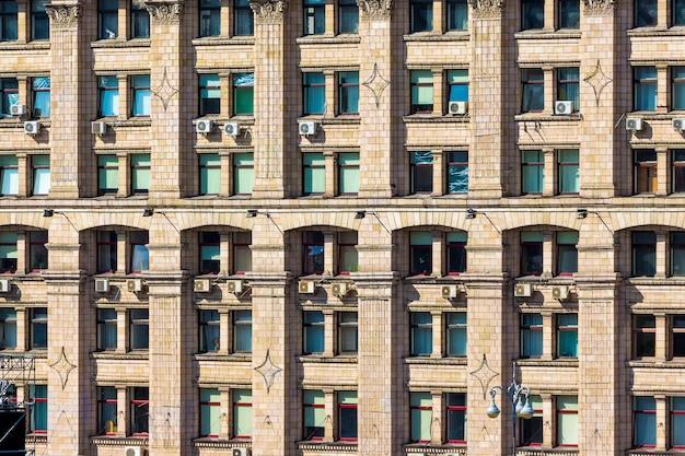 Стена многоэтажного здания с окнами, образующими узор