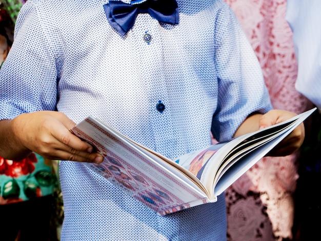 小さな男の子は開いた本を手に持っています