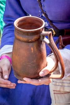 Женщина в средневековой одежде держит в руках глиняный горшок