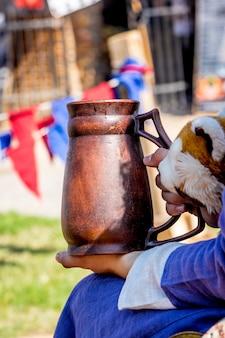 Женщина в средневековой одежде держит глиняный горшок во время фестиваля