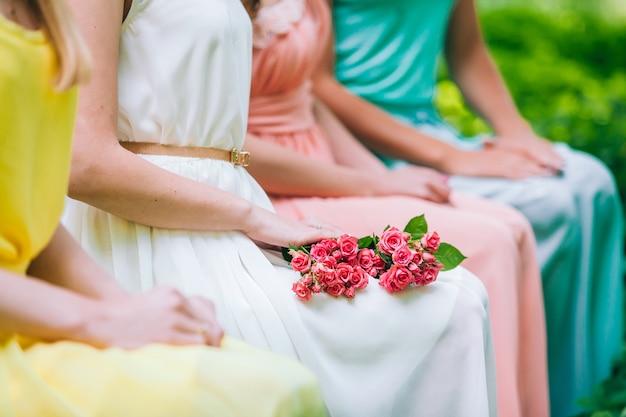 カラフルなカクテルドレスの女の子が花の花束のベンチに座っています。