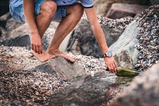 手に時計を持った男が海にメッセージ水を入れたボトルを置く