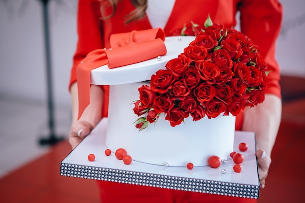 誕生日に手で開催された弓とバラの美しい赤いケーキ。