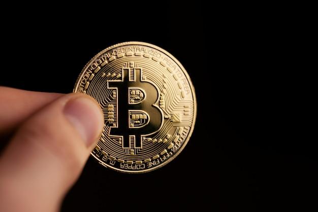 黄金のビットコインコインを持っている手
