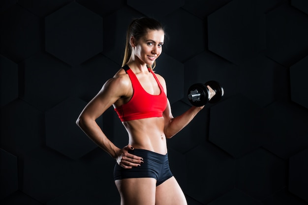 暗闇の中で重みを持つフィットネストレーニングをしている美しい女性