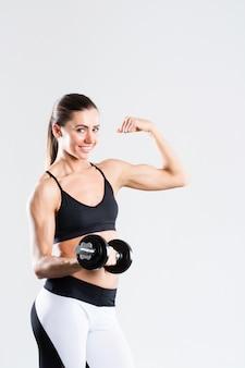 Тренировка женщины с гантелями, изолированная на белизне