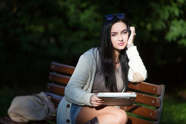 Девушка студент электронный планшет, сидя на скамейке в парке