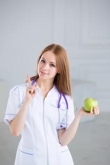 Доктор, держа зеленое яблоко. концепция здорового питания.