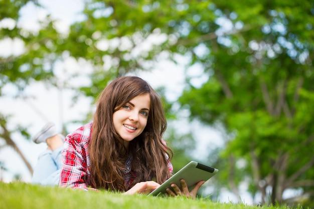 Молодая женщина с цифровым планшетом на траве