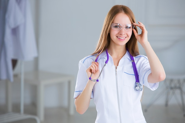 Улыбающиеся женщина семейный врач со стетоскопом. здравоохранение.