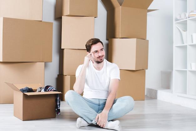 Молодой парень сидит на полу нового дома, окруженного коробками.