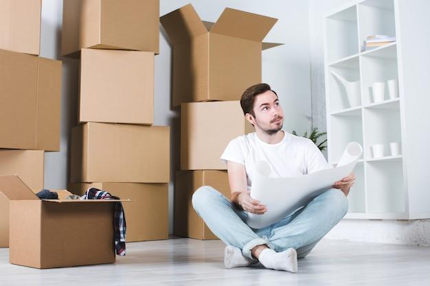 Молодой человек в планах интерьера нового дома.