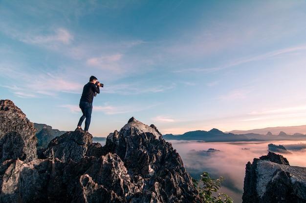 山の頂上に立って、日の出の朝の間に風景写真を撮る若いアジアの写真家