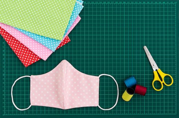 Вид сверху из хлопчатобумажной маски для лица из ткани на зеленой коврике