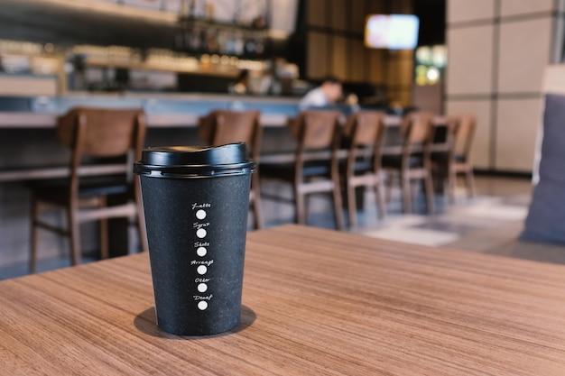 モダンなカフェの木製テーブルにコーヒーカップを奪う