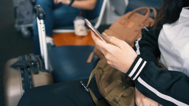 スマートフォンを使用して空港の出発ラウンジで待っている空港で乗客旅行者女性の手を閉じる
