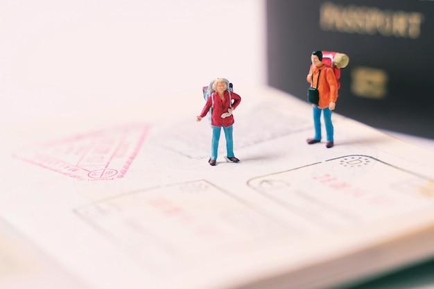 ミニチュアの人々フィギュアバックパックウォーキングと入国スタンプ、旅行や休暇の概念のパスポートページの上に立って