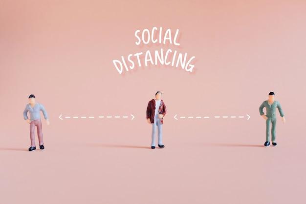 社会的距離の概念、立っているミニチュアの人々は公共の場で距離を保ちます