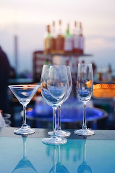 豪華な屋上でバーテンダーのカウンターバーにカクテルとシャンパンの空のグラス