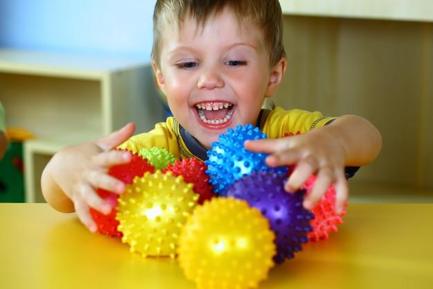 Маленький мальчик играет с цветными шариками