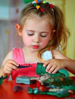 Маленькая улыбающаяся девочка играет дома.