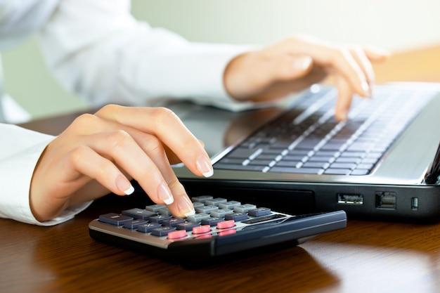 Предприниматель работает в офисе с предметами для ведения бизнеса