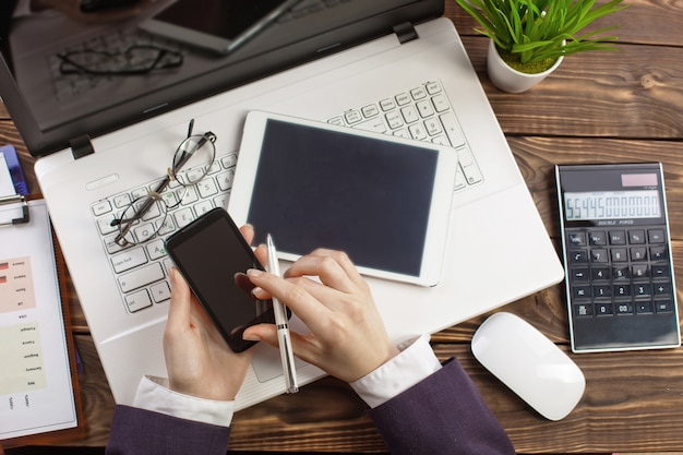 Деловая женщина работает в офисе с предметами для ведения бизнеса