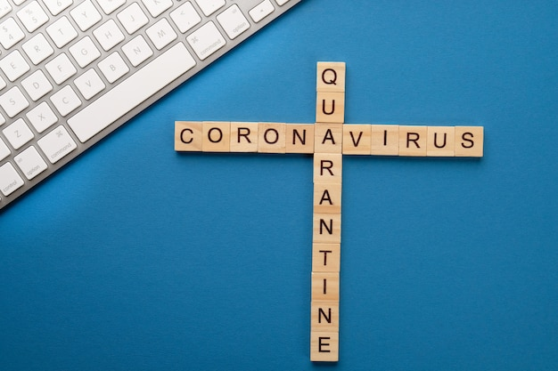 医療をテーマにしたクロスワードと青いテーブル上のコンピューター。パンデミック検疫のコンセプト