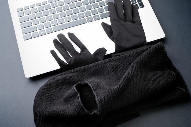 ラップトップ上の黒いマスクと黒い手袋