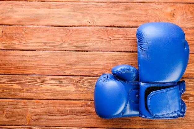 木製の背景に青いボクシンググローブ