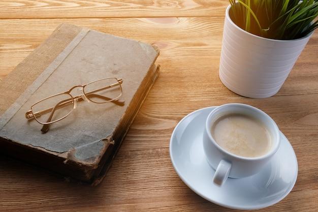 古い本と木製のテーブルの上のコーヒー。朝のコーヒーと本。