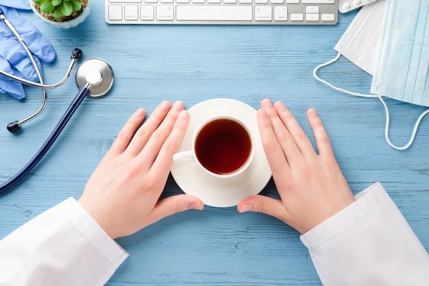 Руки доктора с кофе за столом. стол врача.