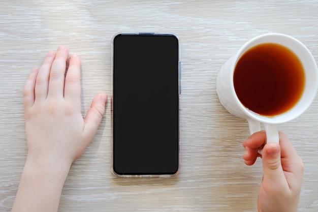 テーブルの上の携帯電話で手。電話を手に持った女の子。