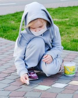 防護マスクを着た子供が通りを歩いています。