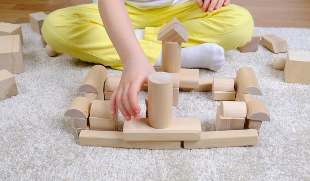 Ребенок играет с деревянными кубиками на полу