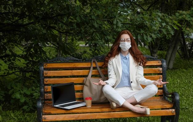Молодая женщина работает на компьютере на улице