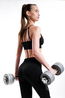 Красивая девушка с гантелями. концепция спорта