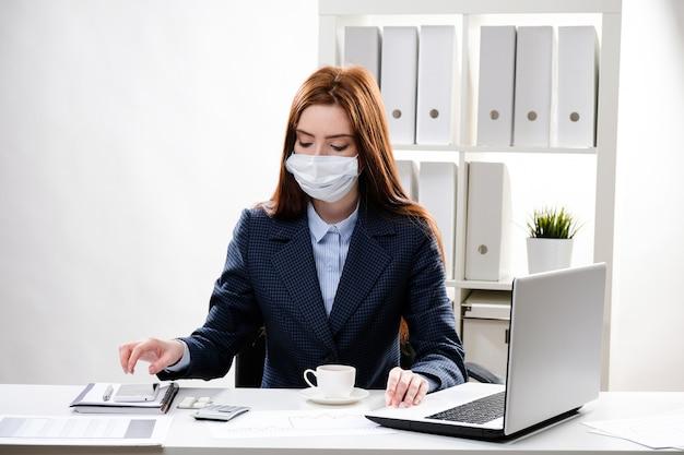 Женщина на рабочем месте в медицинской маске