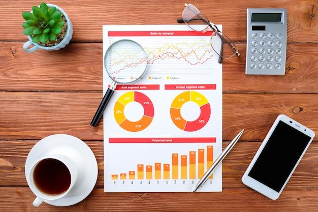 ビジネスグラフ、電話、電卓、木製のテーブルの上のコーヒー