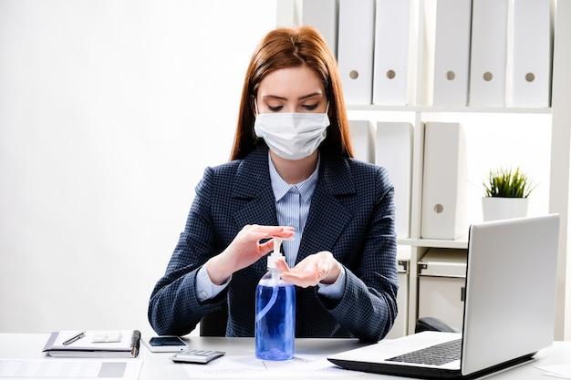 Деловая женщина моет руки гелем на рабочем месте в офисе