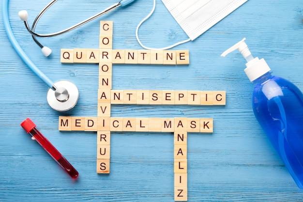 Медицинский кроссворд, мыло, маска, фонендоскоп на синем столе