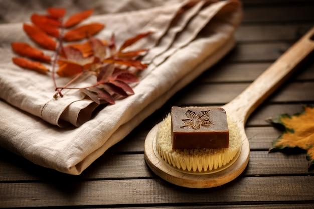 秋の葉を持つ木製の背景に対してボディブラシに有機タルタル石鹸、クローズアップ、サイドビュー