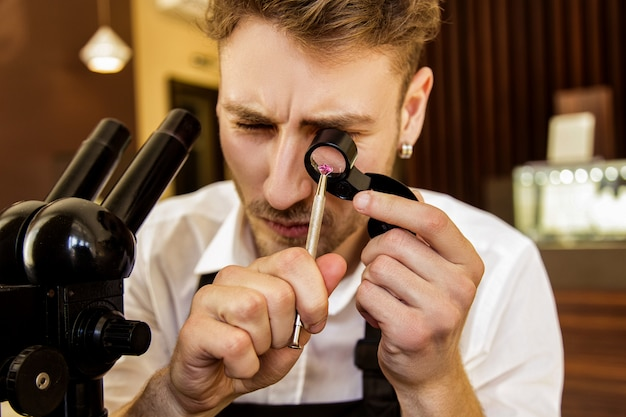 宝石商は虫眼鏡の下で宝石を調べます