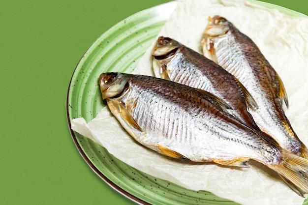 白い背景の上の皿に魚のフライ