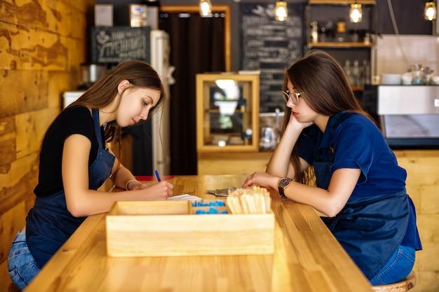 Две милые девушки-бариста сидят за деревянным столом в кофейне