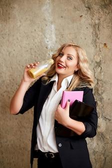 スーツを着た女の子がボトルからジュースを飲んで笑顔。食品配達