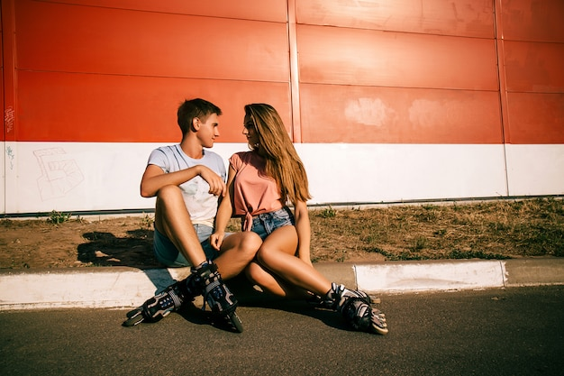 Пара сидит на бордюре на красной стене