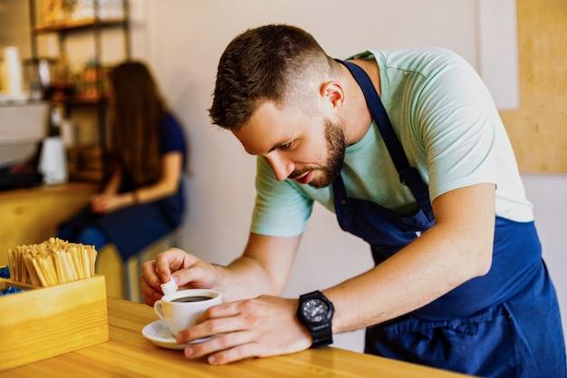 Молодой мужской бариста готовит кофе
